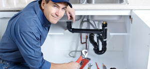 Max Meadows plumber working on drain